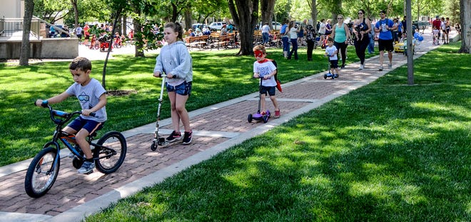 Children and adults make their way along a Stevens Park sidewalk Friday during the Beef Empire Days United Wireless Children's Parade.