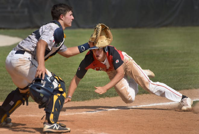 Micah Smith of New Boston Huron dives into home plate safely on a squeeze bunt put down by Matthew Williams as Huron beat Trenton in the Division 2 quarterfinals at Concordia University Saturday. Catching for Trenton Brock Beaudrie.