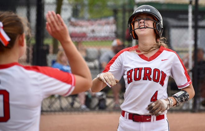 New Boston Huron's Emma Sic scores the first run against Garden City in the Division 2 Regional semifinals Saturday morning. Emma had all four wisdom teeth removed this past Monday.