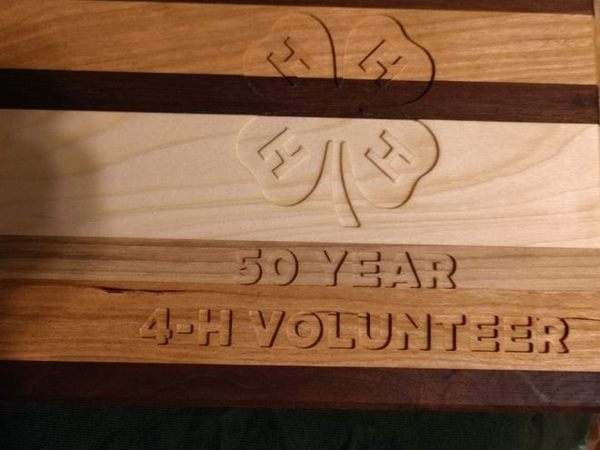 """Both Barbara Siebarth and Dennis and Bev the Winter received a hand-carved, wooden cutting board (above) from MSU Extension recognizing them for 50 years or more of service to 4-H. Engraved on the board is a 4-H clover and the words """"50-year 4-H volunteer."""""""
