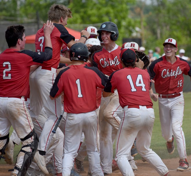 New Boston Huron players celebrate a solo home run hit by Cole Grunwald (center) in the Division 2 quarterfinals against Trenton at Concordia University Saturday. Huron won 7-5 to earn a spot in the state semifinals.