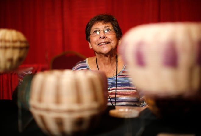 Cherokee basket maker Mary Aitson shows some of her work at her booth Saturday during the Red Earth Festival at Grand Casino & Hotel Resort in Shawnee.