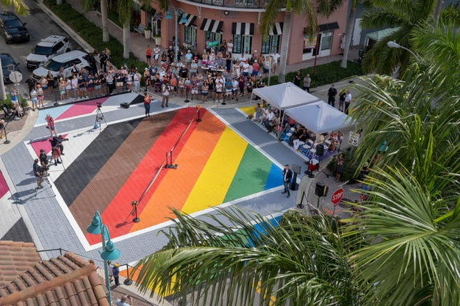 """People gather for the dedication of the """"Pride Intersection"""" at Northeast Second Avenue and Northeast First Street in the Pineapple Grove Arts District in Delray Beach on Saturday. The Progress Pride Flag adds five colors to the iconic six-color Rainbow Pride Flag. GREG LOVETT/PALM BEACH POST"""