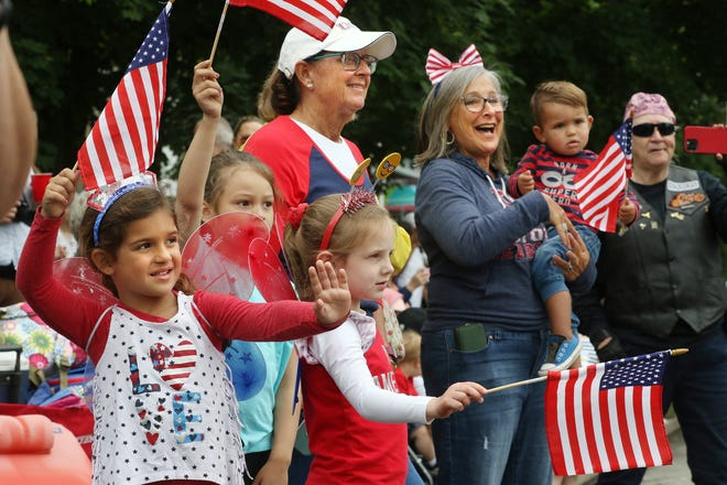 Spectators in patriotic attire wave as the parade passes by.