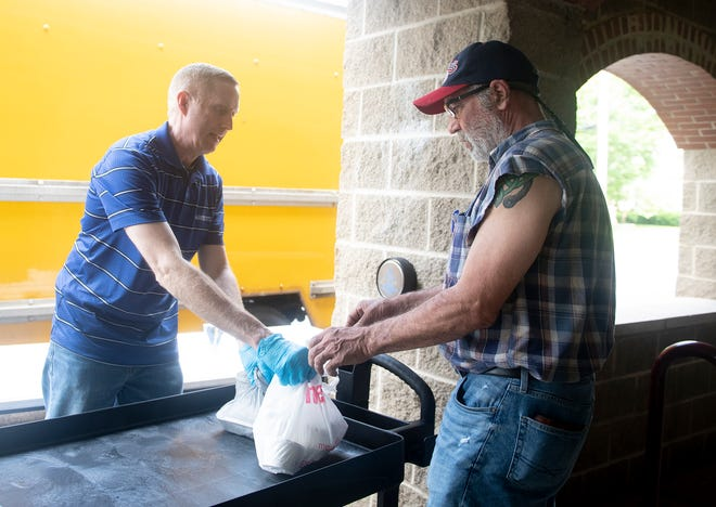 Newman Center Knights of Columbus and Trinity Lutheran Church in Kent work together to serve free lunches at the church for the Lord's Lunch. Pulled pork sandwiches, potato salad, grapes, cookies and drinks were available. Glenn Leppo hands off lunches.