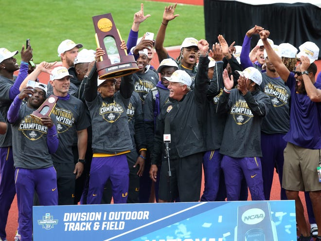 Louisiana State University athletes and their coach Dennis Shaver, center, celebrate after LSU captures the NCAA Outdoor Track and Field Championship in Eugene, Ore. June 11, 2021