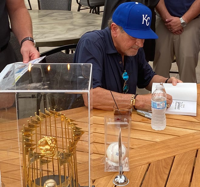 """Former Kansas City Royal Greg Pryor signs his book, """"The Day The Yankees Made Me Shave,"""" during a reception Friday night in downtown Salina."""