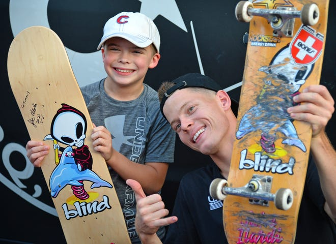 Timmy Phelan, 11, of Sarasota, poses with Jake Ilardi, a professional street skateboarder who recently clinched a berth on the first-ever U.S. Olympic skateboarding team, during a Friday evening celebration held for Ilardi, 24, at Compound Boardshop in Sarasota.
