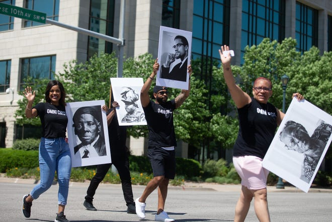 Members of Omni Circle Group hold signs of prolific Black leaders during June 12's Juneteenth parade through downtown Topeka.