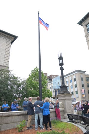 U.S. Sen. Elizabeth Warren, U.S. Rep. James McGovern and Juneteenth organizer Fred Taylor raise the Juneteenth flag during a ceremony on Saturday at Worcester City Hall.