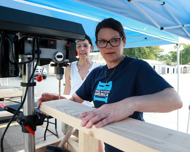 Kari Fry looks on as Tress Fry pulls boards along the covered assembly line to the drill press, Saturday, June 12, as they joined other volunteers in the Lowe's parking to build beds for the Sleep In Heavenly Peace building day.