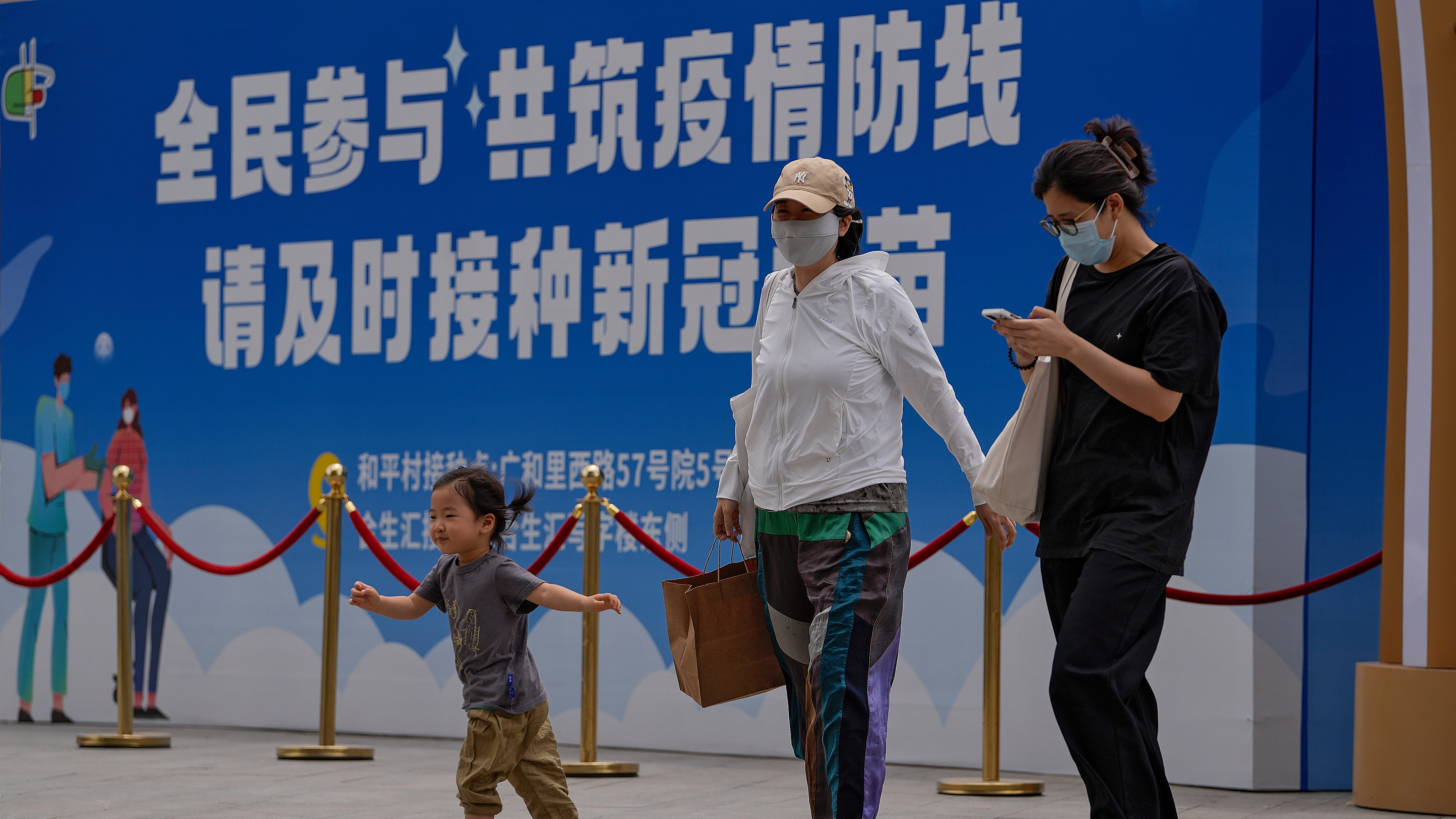 """Women wearing face masks to help curb the spread of the coronavirus and a child walk by a billboard showing the words """"All people participate in building a line of defense against the epidemic, please get the vaccine in time"""" on display outside a shopping mall in Beijing on May 24, 2021."""