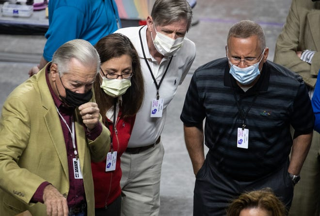 Wisconsin state Reps. Rachael Cabral-Guevara, second from left, and Chuck Wichgers, right, watch as Maricopa County ballots from the 2020 general election are examined and recounted by contractors hired by the Arizona Senate on June 12, 2021, at Veterans Memorial Coliseum in Phoenix.