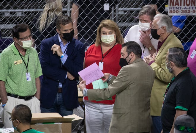 Wisconsin state Rep. Janel Brandtjen, center, former Missouri Gov. Eric Greitens, second from left, and Wisconsin state Rep. Dave Murphy, left, watch as Maricopa County ballots from the 2020 presidential election are examined and recounted by contractors hired by the Arizona Senate on June 12, 2021, at Veterans Memorial Coliseum in Phoenix.  Election Audit 13p1
