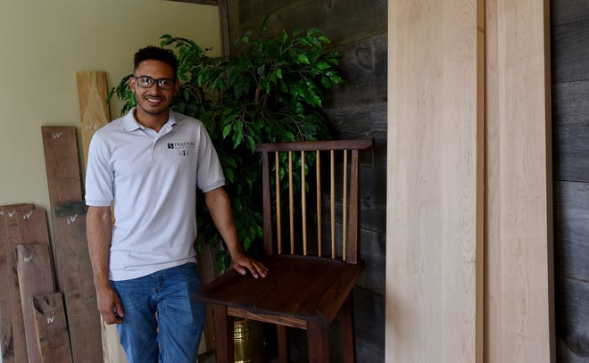 Jonathan Stratton, who makes custom furniture from his Granville workshop, poses with the first piece of furniture he constructed, a chair made of black American walnut with white oak spindles.