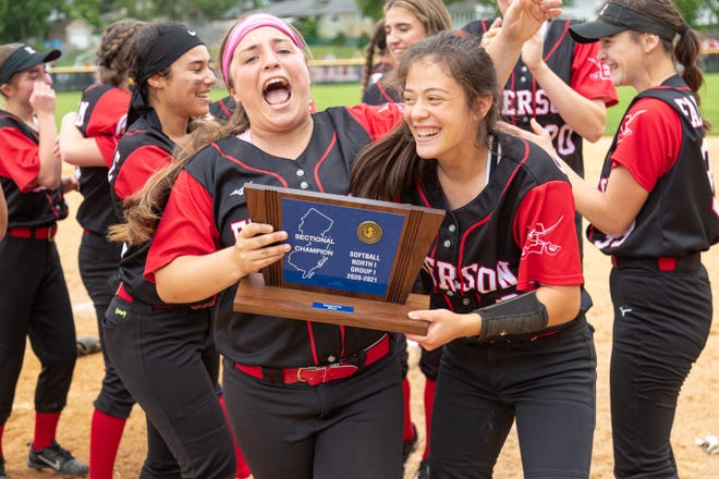 Emerson seniors Ashlyn Sterinsky (left) and Amanda Sallemi brandish the trophy after the Cavos won the North 1, Group 1 softball sectional title in Emerson, N.J. on Saturday, June 12, 2021.