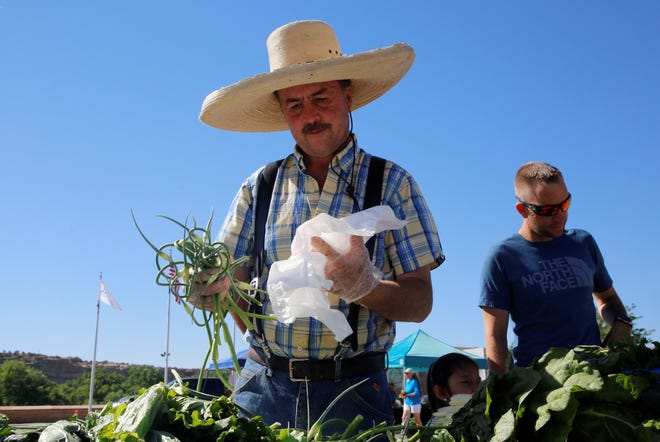 Vernon Bridgewater of Bridgewater Gardens places garlic scapes in a plastic bag for a customer on June 12 at the Farmington Growers Market.