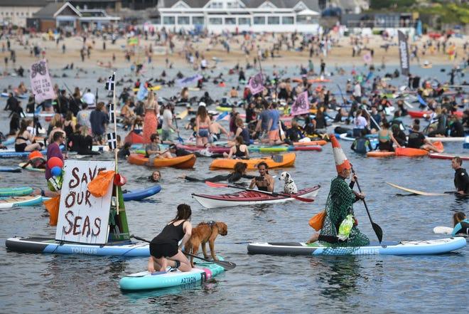 Des surfeurs, des paddleboarders et des kayakistes participent à une manifestation environnementale dans l'eau au large de la plage de Gyllyngvase à Falmouth, en Cornouailles, lors du sommet du G7.