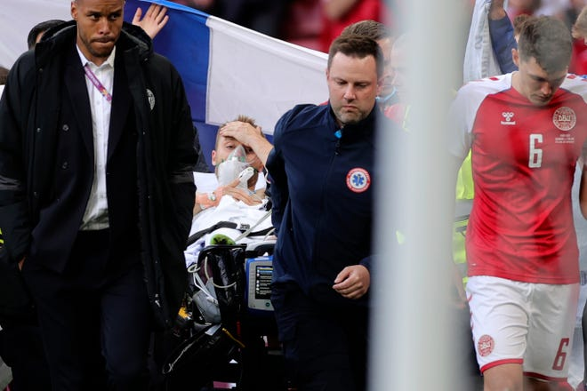Paramedics use a stretcher to take Christian Eriksen off the field.