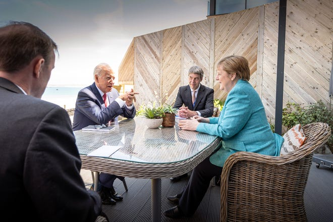 President Joe Biden and German Chancellor Angela Merkel met on the sidelines of the G7 summit in St Ives, England.  With them are foreign policy advisers Jan Hecker and Jake Sullivan.