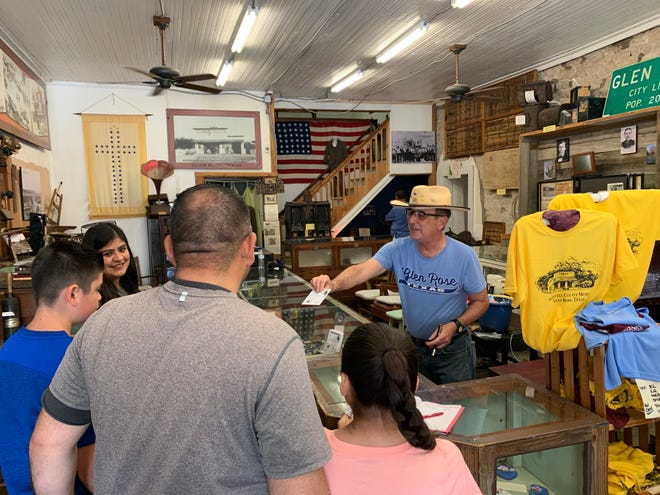 Museum tour guide Dennis Moore hands out dinosaur hunting licenses to a family from Harlingen at the Somervell County Museum in Glen Rose, Texas.