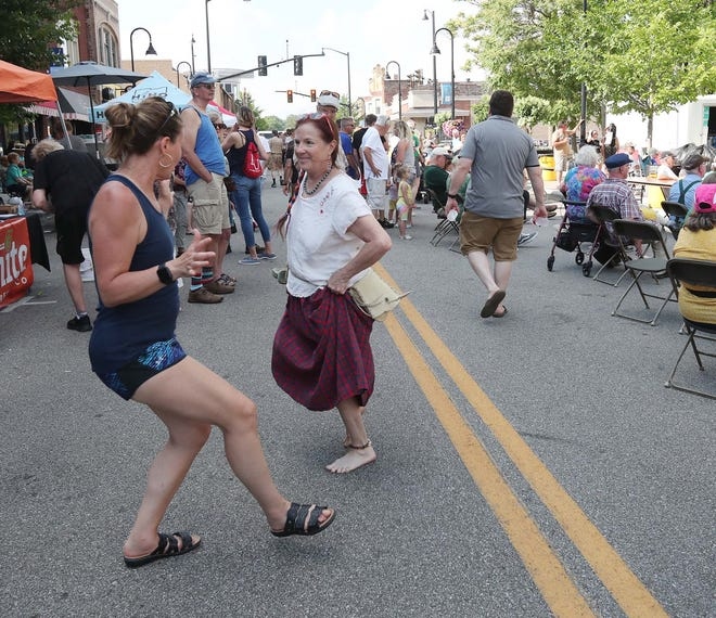 Lin Danes, left, of Kent, dances with Catrina Kolesar of Stow on Front Street to Irish music during the Riverfront Irish Festival Sunday, June 13, 2021 in Cuyahoga Falls, Ohio.