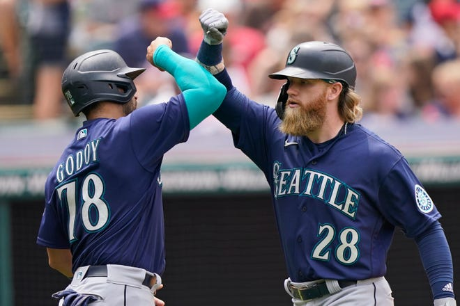 Seattle Mariners' Jake Fraley, right, and Jose Godoy celebrate after Fraley hit a two-run home run in the fourth inning of a baseball game against Cleveland, Sunday, June 13, 2021, in Cleveland. (AP Photo/Tony Dejak)