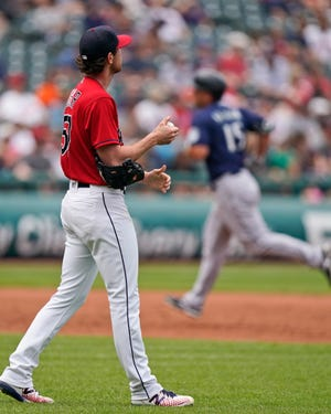 Cleveland starting pitcher Shane Bieber, left, waits for Seattle Mariners' Kyle Seager to run the bases after Seager hit a solo home run in the third inning of a baseball game, Sunday, June 13, 2021, in Cleveland. (AP Photo/Tony Dejak)