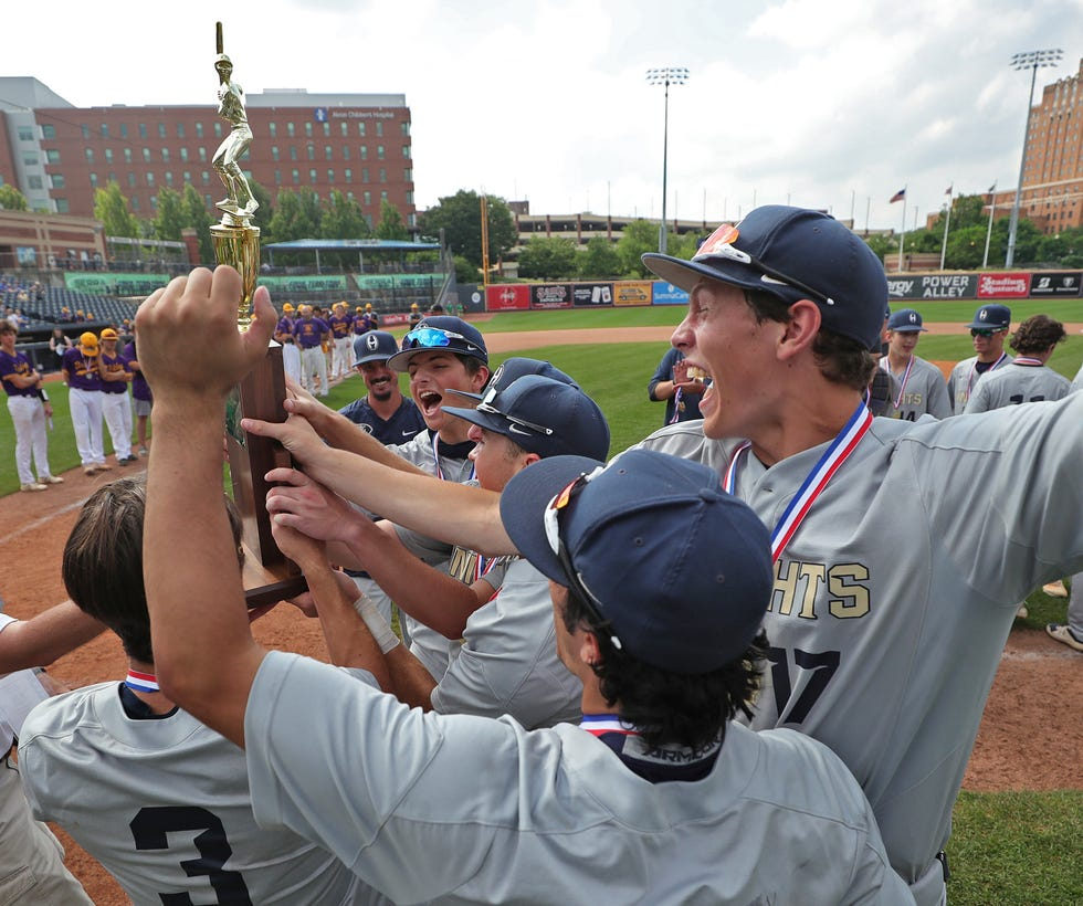 Hoban baseball players hoist up the Division II state championship trophy after beating Bloom-Carroll, 2-1, at Canal Park on Sunday, June 13, 2021, in Akron, Ohio. [Jeff Lange / Akron Beacon Journal]