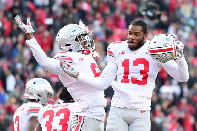 Nov 17, 2018; College Park, MD, USA;  Ohio State Buckeyes cornerback Kendall Sheffield (8) and cornerback Tyreke Johnson (13)  celebrate on the field after defeating Maryland Terrapins in overtime at Capital One Field at Maryland Stadium. Mandatory Credit: Tommy Gilligan-USA TODAY Sports