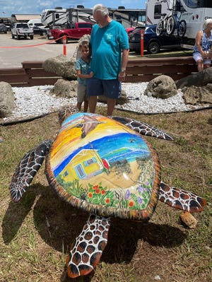 Artist Stewart Maxcy and his grandson, Stephen, stand behinc 'Beverly' on Saturday in Beverly Beach.