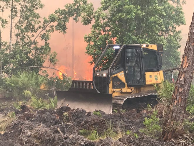 Bulldozers from the Florida Forest Service cut lines around a 2,200-acre forest fire at Possum Camp Road near New Smyrna Beach. The fire started Saturday afternoon and by Sunday morning, had grown to an estimated 2,200 acres.
