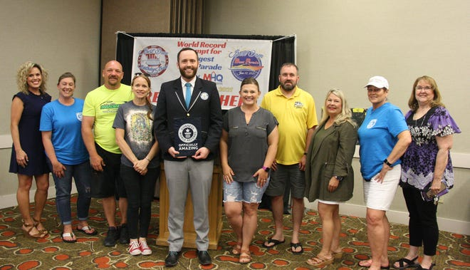 """Mark Marcotte, an adjudicator with the Guinness Book of World Records presents an """"Officially Amazing"""" plaque to Best Dam Boat Parade committee members."""