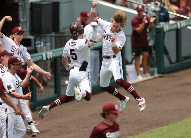 Mississippi State's Rowdey Jordan, right, and Tanner Allen celebrate Allen's home run in the first inning of an NCAA college baseball super regional game against Notre Dame, Saturday, June 12, 2021, in Starkville, Miss. Mississippi State won 9-8. (Adam Robison/The Northeast Mississippi Daily Journal via AP)