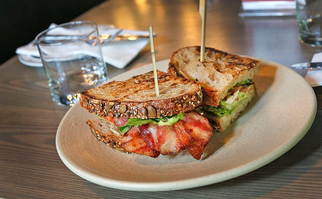 A BLT on seeded sourdough bread with sesame and pepitas seeds is plated at Steel & Rye in Milton on Sunday, June 13, 2021. The restaurant features its own artisan bakery selling breads, sandwiches and pastries.