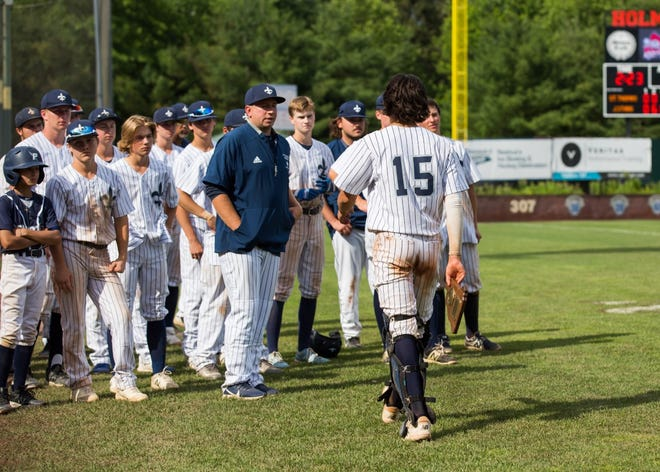 St. Thomas Aquinas senior catcher Adam Stewart walks back to his team after receiving the Division II runner-up plaque following Saturday's 10-3 loss to John Stark at Holman Stadium in Nashua.