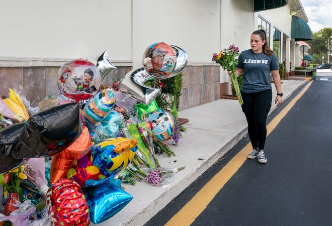 Katie Howey brings flowers to a memorial in front of a Publix Super Market in Royal Palm Beach, Florida on June 13, 2021. Timothy Wall shot and killed a 69-year-old grandmother and her toddler grandson inside the store before killing himself on Thursday. Greg Lovett/The Palm Beach Post