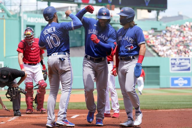 Blue Jays right fielder Teoscar Hernandez, center right, who went 6-for-6, celebrates with Marcus Semien and Bo Bichette, right, after hitting a three-run home run in the first inning of Sunday's game against the Red Sox.