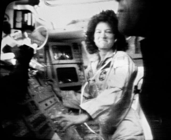 Astronaut Sally Ride is shown at work aboard the space shuttle Challenger on June 18, 1983, as the crew prepared to deploy the ANIK satellite. Ride is the first American woman to go into space.