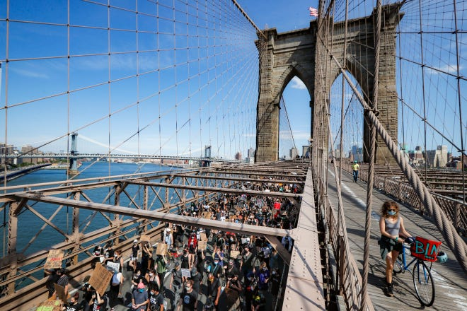 Protesters march over the Brooklyn Bridge toward Manhattan following a Juneteenth rally in Cadman Plaza Park, on June 19, 2020, in New York. Juneteenth marks the day in 1865 when federal troops arrived in Galveston, Texas, to take control of the state and ensure all enslaved people be freed, more than two years after the Emancipation Proclamation.