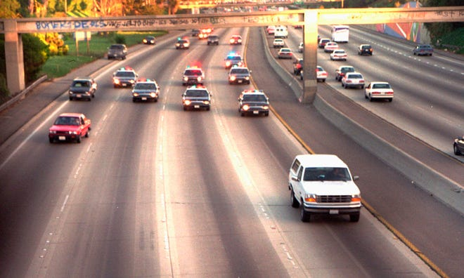 In this June 17, 1994, photo, a white Ford Bronco driven by Al Cowlings and carrying O.J. Simpson, is trailed by police cars as it travels on a southern California freeway in Los Angeles. Cowlings and Simpson led authorities on a chase after Simpson was charged with two counts of murder in the deaths of his ex-wife and her friend. The slow-speed chase across freeways was televised nationally and ended when police persuaded Simpson to surrender.