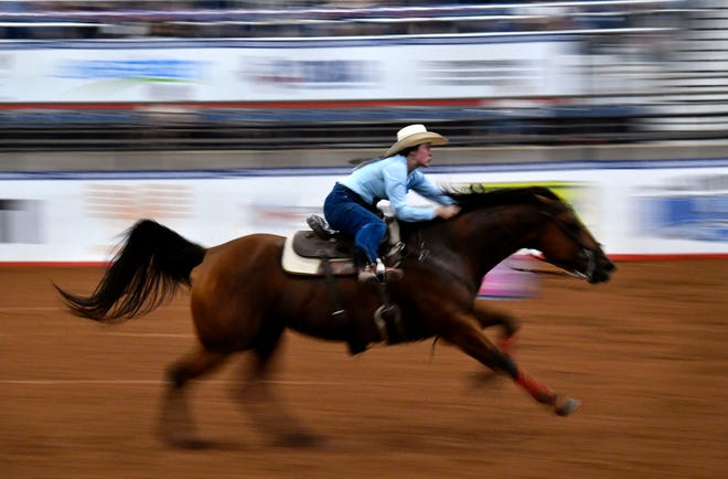Whitley Burns speeds across the Taylor Telecom Arena at the end of her barrel racing circuit during Wednesday's Texas High School Rodeo Finals.