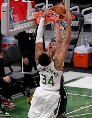 Bucks forward Giannis Antetokounmpo dunks over Brooklyn's Blake Griffin during the third quarter Sunday at Fiserv Forum. Antetokounmpo led all scorers with 34 points.