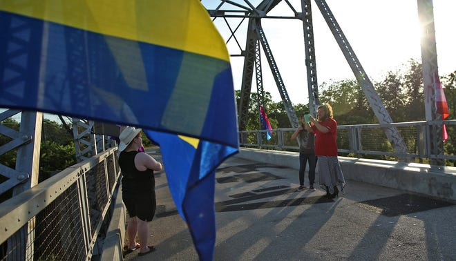 People take photos with pride flags strung on the Lone Wolf Bridge in San Angelo after a vigil for the victims of the 2016 Pulse nightclub shooting in Orlando, FL on Saturday, June 12, 2021.