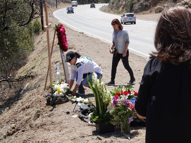 Ana Pozza, in white jersey, arranges flowers at a roadside memorial for her son, Joseph Terharutyunyan, 20, on Kanan Dume Road before a memorial cruise on Sunday.