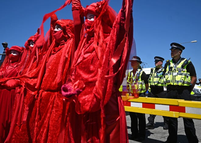 Police monitor the 'Red Brigade' group from the Extinction Rebellion environmental activists as they protest in the streets of Falmouth, Cornwall during the G7 summit on June 12, 2021.