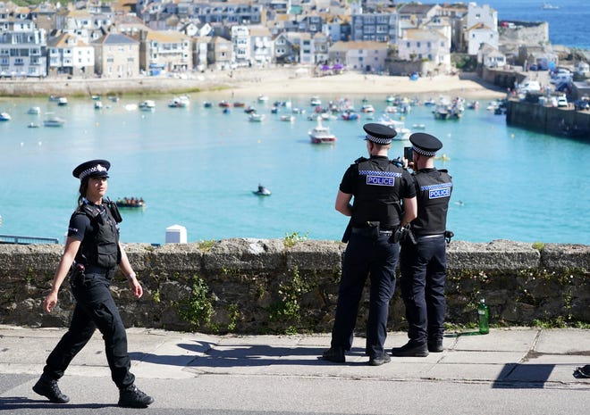 Police officers photograph the route of President Joe Biden's convoy after attending a church service with First Lady Jill Biden in St Ives, Cornwall, England, on June 13, 2021.