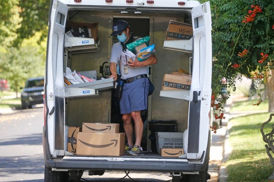 A United States Postal Service carrier delivers mail to homes in 2020 in Salt Lake City.