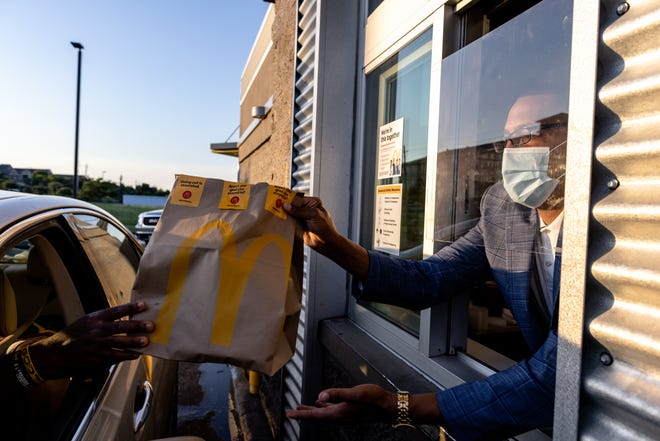 E.W. Ross hands a bag of food to a customer in the drive-thru window of his McDonald's restaurant in north Austin on Sunday, June 13, 2021.