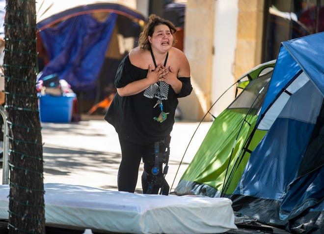 """Morgan """"Smokey"""" Quarts cries out as she is forced to move her belongings from a homeless encampment near City Hall on Monday. Austin voters approved the return of the camping ban last month."""